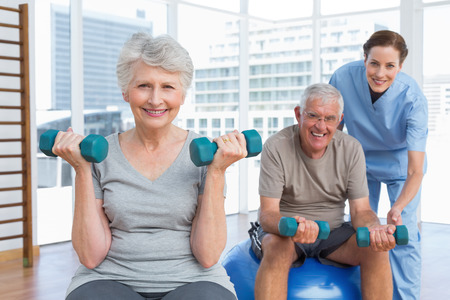Female therapist assisting senior couple with dumbbells in the medical office photo