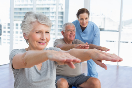 female therapist: Female therapist assisting senior couple with exercises in the medical office Stock Photo