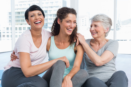 laughter: Cheerful fit women sitting in the yoga class