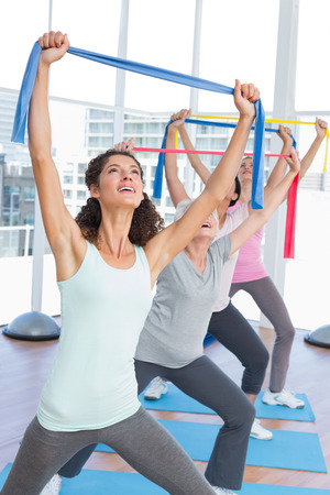 Happy female trainer with class holding up exercise belts at yoga class photo