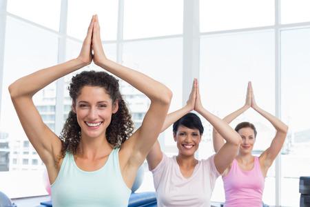 manos unidas: Retrato de la mujer joven deportiva con las manos juntas sobre la cabeza en el estudio de fitness Foto de archivo