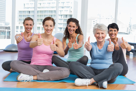Full length portrait of happy women gesturing thumbs up in the yoga class photo