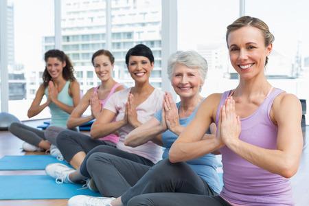 joined hands: Entrenador Mujer y la clase sentados con las manos juntas en una fila en la clase de yoga