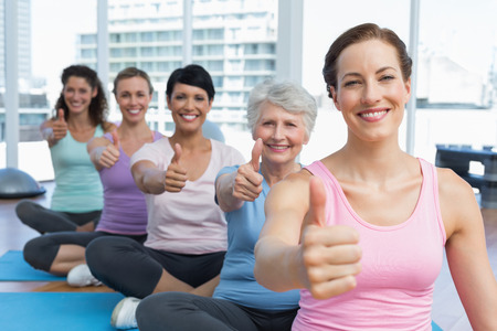 Portrait of smiling women gesturing thumbs up in the yoga class photo
