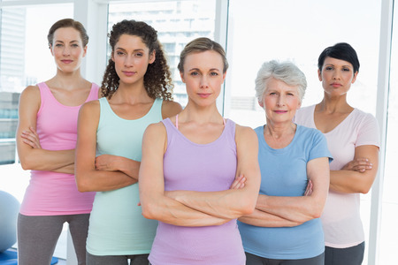 Portrait of confident women with arms crossed standing in the yoga class photo
