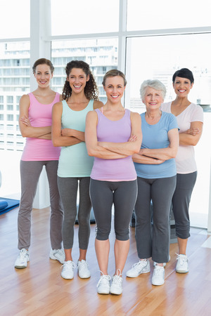 Portrait of happy women with arms crossed standing in the yoga class photo