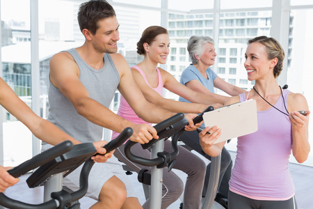 Trainer walking along people working out at spinning class in gym photo