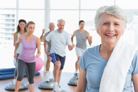 physical: Portrait of a cheerful senior woman with people exercising in the background at fitness studio