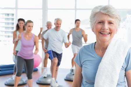 Portret van een vrolijke senior vrouw met mensen te oefenen op de achtergrond in fitness-studio