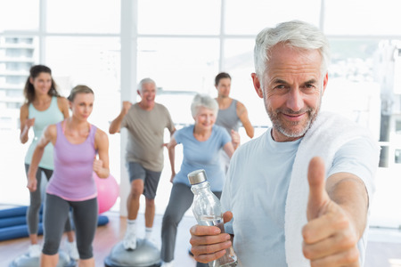 Happy senior man gesturing thumbs up with people exercising in the background at fitness studio