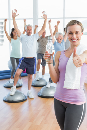 Young woman gesturing thumbs up with people stretching hands in the background at fitness studio photo
