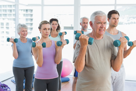 aerobic instructor: Fitness class exercising with dumbbells in a bright gym Stock Photo