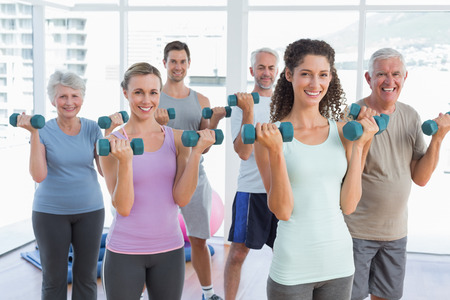 Fitness class exercising with dumbbells in a bright gym Stock Photo