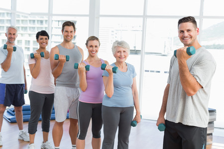 Fitness class exercising with dumbbells in a bright gym photo