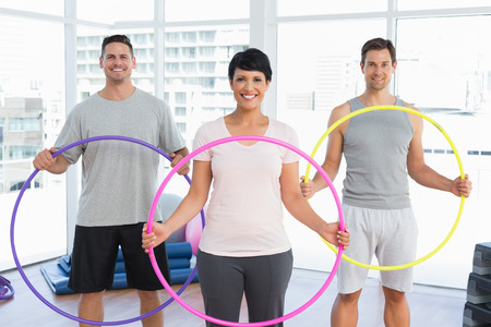 body toning: Portrait of fitness class holding hula hoops in bright gym