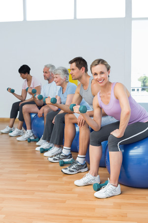 Side view of fitness class with dumbbells sitting on exercise balls in a bright gym photo