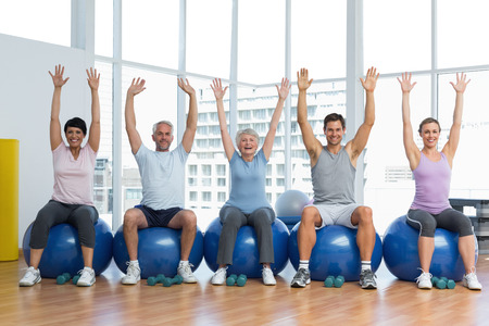 Portrait of fitness class sitting on exercise balls and raising hands in a bright gym