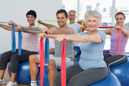 Class holding out exercise belts while sitting on fitness balls in yoga class photo
