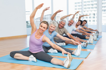 pilates man: Happy female trainer with class stretching hands at yoga class