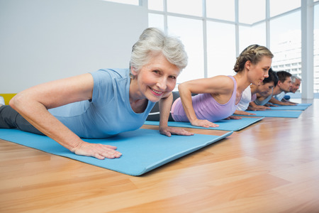 pilates man: Fitness group doing cobra pose in row at the yoga class
