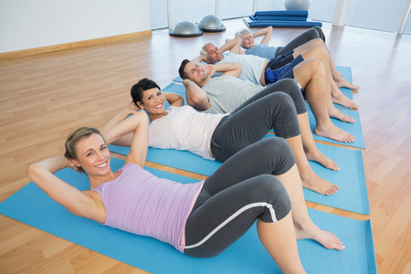 Side view portrait of fitness class lying on mats in row at yoga class photo