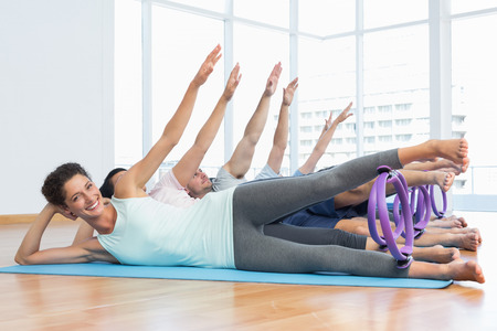 Full length of fitness class stretching legs and hands in row at yoga class photo