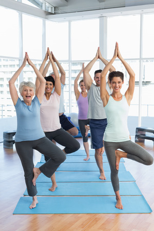 Portrait of a smiling trainer with class standing in tree pose at yoga class photo