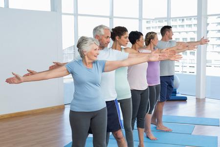Portret van fitness klasse handen uitrekken in rij op yogales Stockfoto