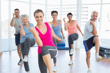 Portret van lachende mensen uit het doen van de macht fitness oefening op yogales in fitness-studio