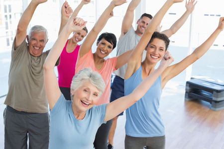 Portrait of smiling people doing power fitness exercise at yoga class in fitness studio photo