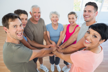 Portrait of happy sporty people holding hands together in the yoga class Stock Photo