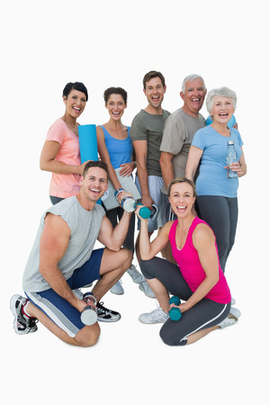 Full length portrait of happy fitness class over white background photo