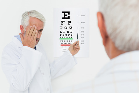 Male pediatrician ophthalmologist with senior patient pointing at eye chart in medical office photo
