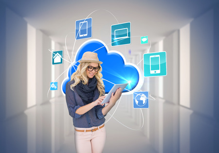 Digital composite of stylish blonde using tablet pc with app icons and cloud photo