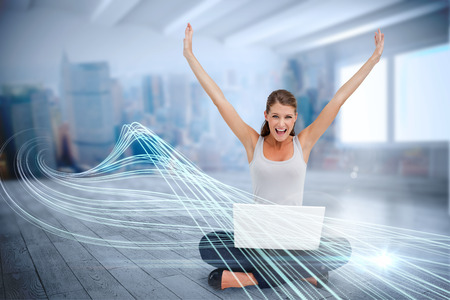 Digital composite of cheering blonde using laptop with clouds Stock Photo