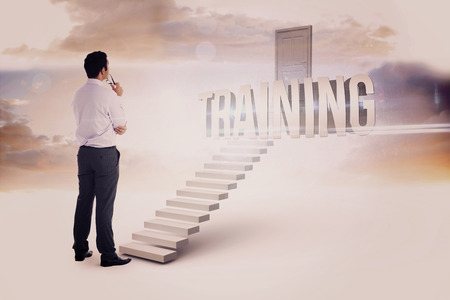 business training: The word training and businessman holding glasses against white steps leading to closed door
