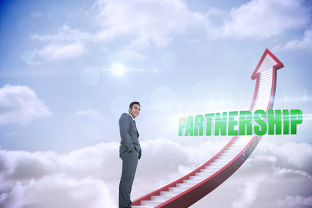 The word partnership and smiling businessman standing against red stairs arrow pointing up against sky photo