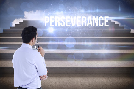 perseverance: The word perseverance and businessman holding glasses against steps against blue sky