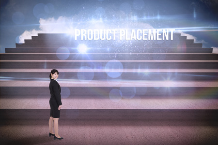 The word product placement and smiling businesswoman against steps against blue sky Stock Photo