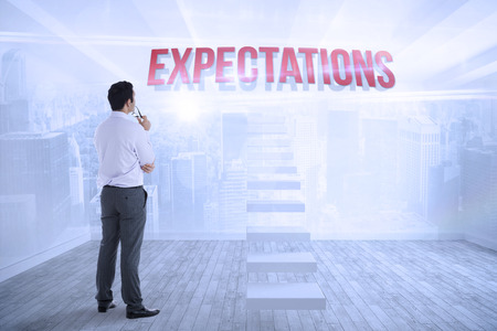 The word expectations and businessman holding glasses against city scene in a room Stock Photo