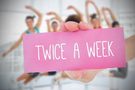 Woman holding pink card saying twice a week against dance class in gym photo