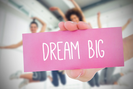 Woman holding pink card saying dream big against fitness class in gym Stock Photo
