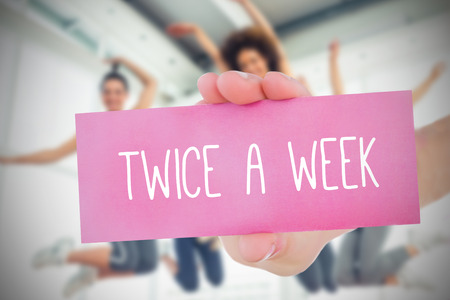 Woman holding pink card saying twice a week against fitness class in gym photo