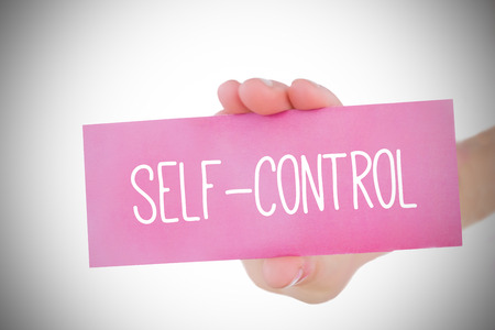selfcontrol: Woman holding pink card saying self control against white background with vignette Stock Photo