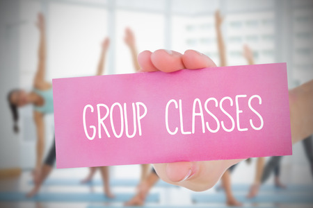Woman holding pink card saying group classes against fitness class in gym photo