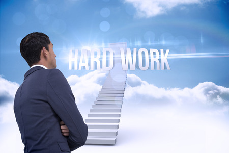 hard work: The word hard work and unsmiling asian businessman with arms crossed against shut door at top of stairs in the sky