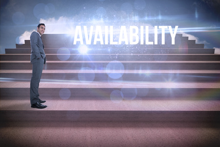 The word availability and smiling businessman standing against steps against blue sky