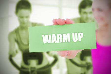 warm up: Scheda della holding bionda Fit dicendo riscaldare contro classe spinning in palestra