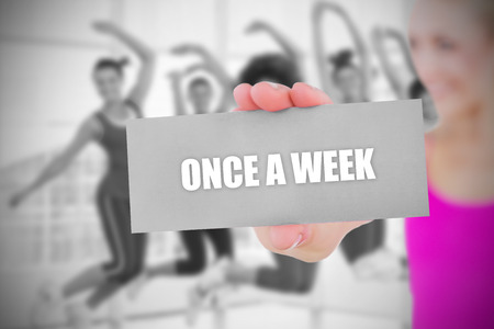 Fit blonde holding card saying once a week against  dance class in gym  photo