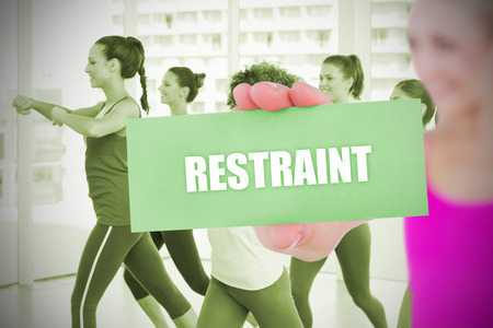 restraint: Fit blonde holding card saying restraint against  dance class in gym